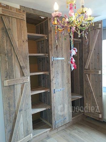 Steigerhouten inbouwkast open legplanken en kledingstang van steigerbuis